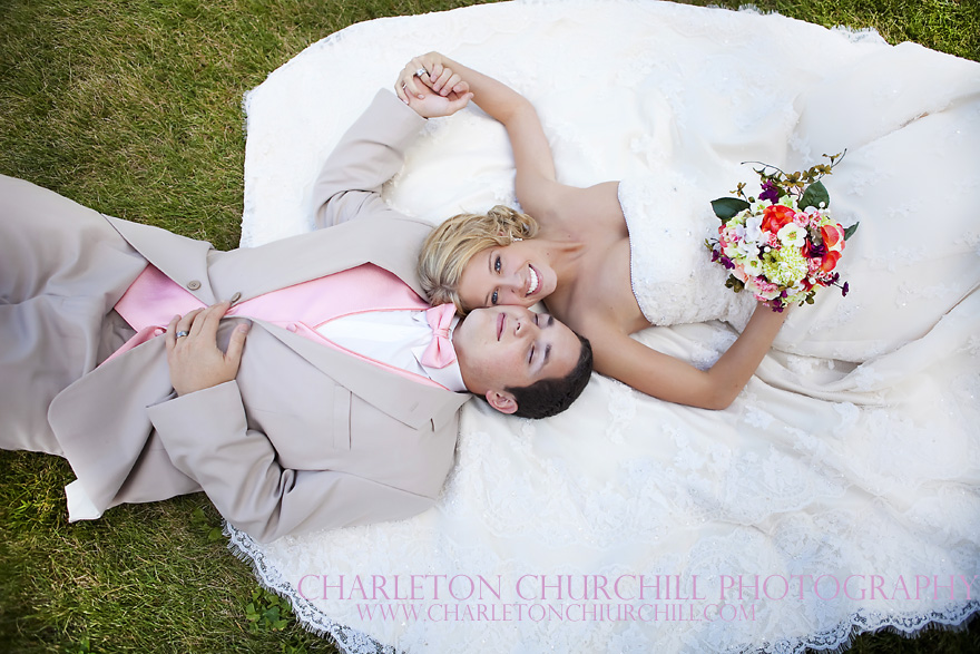 bride and groom laying on the grass