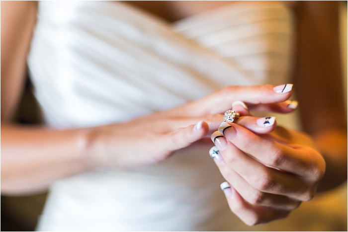 bride ring on finger with bridal dress reflecting the sun outside